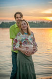 A pregnant beautiful woman with her husband on the river bank beach smiling and touching her belly with love and care Stock Image