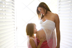 Pregnant Belly. Pregnant women and daughter kissing her belly Stock Photography
