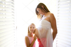 Pregnant Belly. Pregnant women and daughter listening to belly Royalty Free Stock Photo