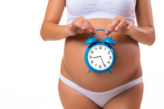Pregnant belly with alarm clock. Conceptual image. Soon birth. Royalty Free Stock Image