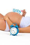 Pregnant belly with alarm clock. Soon birth. Fetal development by months. Happy pregnancy. Pregnant belly with alarm clock. Soon birth. Fetal development by Stock Photo