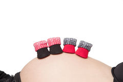 Pregnant belly with baby booties Royalty Free Stock Photo