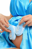 Pregnant belly with blue booties Stock Photos