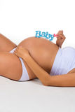Pregnant belly with blue label for newborn baby boy. Stock Photos