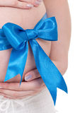 Pregnant belly with blue ribbon. Isolated over a white background. Third trimester royalty free stock photos