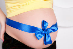 Pregnant belly with blue ribbon. Close up horizontal photo stock image