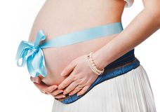 Pregnant belly with blue ribbon - isolated over a white background. Third trimester royalty free stock images