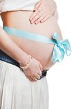 Pregnant belly with blue ribbon - isolated over a white backgrou Stock Photo