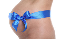 Pregnant belly with blue ribbon Royalty Free Stock Photo