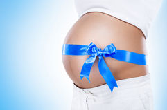 Pregnant belly with blue ribbon Stock Photo
