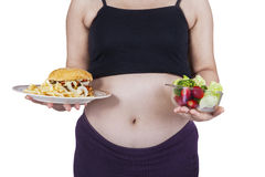 Pregnant belly and choice foods Stock Photo