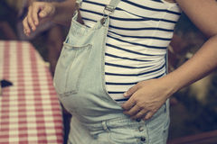 Pregnant belly close up portrait on jeans and striped white shirt Stock Photography
