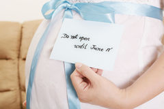 Pregnant belly with a light blue ribbon and a tag saying do not Stock Photos