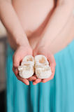 Pregnant belly with newborn baby booties. Pregnant belly with newborn knitted baby booties, soft focus Stock Image