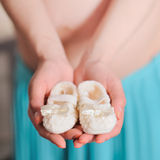 Pregnant belly with newborn baby booties. Pregnant belly with newborn knitted baby booties, soft focus Stock Photography