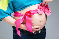 Pregnant belly with pink ribbon. Third trimester royalty free stock photos