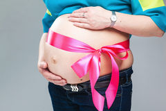 Pregnant belly with pink ribbon. Stock Image