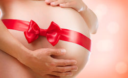 Pregnant Belly. Pregnancy. Pregnant Belly with Red Bow. Pregnancy Stock Images