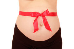 Pregnant belly with red bow Royalty Free Stock Image