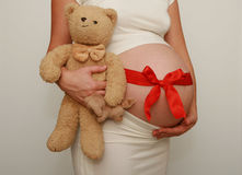 Pregnant belly with red ribbon Royalty Free Stock Image