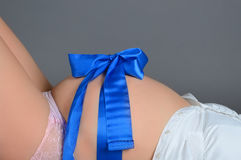 Pregnant belly with a ribbon. Pregnant belly with a blue ribbon royalty free stock image