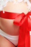 Pregnant belly with ribbon. Pregnant belly with red ribbon in white underwear royalty free stock image