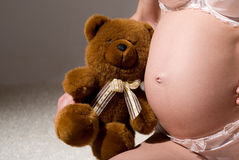 Pregnant belly with Teddy bear Royalty Free Stock Images