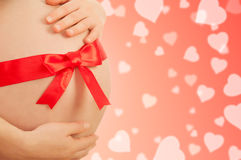 Pregnant belly  of woman with red ribbon Stock Photo