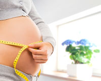 Pregnant belly of a young woman in a beautiful interior Stock Photos