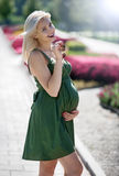 Pregnant blond girl in a green dress Royalty Free Stock Photos