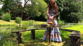 Pregnant blonde girl sit in park sunshine on wooden bench Stock Image