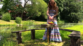 Pregnant blonde girl sit in park sunshine on wooden bench. Nice pregnant woman sit in the garden park in the sunshine with fruit basket on wooden bench stock video