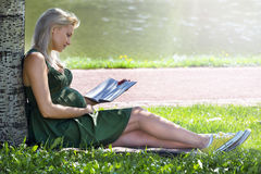 Pregnant blonde girl sits under a tree Stock Photo