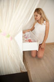 Pregnant blonde near chest of drawers Stock Image