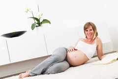 Pregnant blonde woman in her home. Royalty Free Stock Image