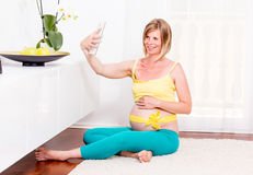 Pregnant blonde woman in her home. Pregnant woman resting at home stock photography