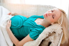 Pregnant blonde woman relaxing on sofa, reading book, dreaming, Royalty Free Stock Images