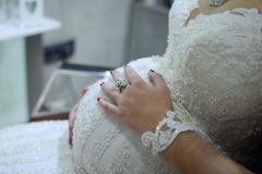 Pregnant woman in wedding dress, with hands holding stomach royalty free stock image
