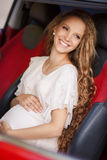 Pregnant brunette girl and her red car Stock Photos