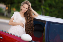 Pregnant brunette girl and her red car Stock Image