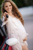 Pregnant brunette girl and her red car Stock Photo