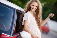 Pregnant brunette girl and her red car Royalty Free Stock Image