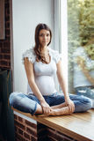 Pregnant brunette girl sitting on the windowsill. Beautiful pregnant brunette girl sitting on the windowsill. Outside is green, the girl is in white T-shirt and stock image