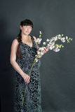Pregnant brunette woman on dark background with flower Stock Photography