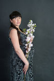 Pregnant brunette woman on dark background with flower Stock Images