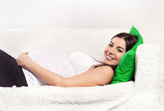 Pregnant brunette woman relaxing on the sofa Stock Photography
