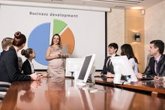 Pregnant business consultant. Answering a question during a meeting at office Royalty Free Stock Images
