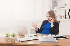 Pregnant business lady at work talking on phone Stock Photography