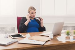 Pregnant business lady at work talking on phone Royalty Free Stock Photo