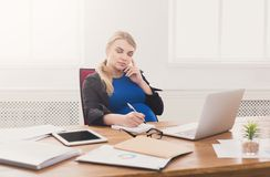Pregnant business lady at work talking on phone Stock Images